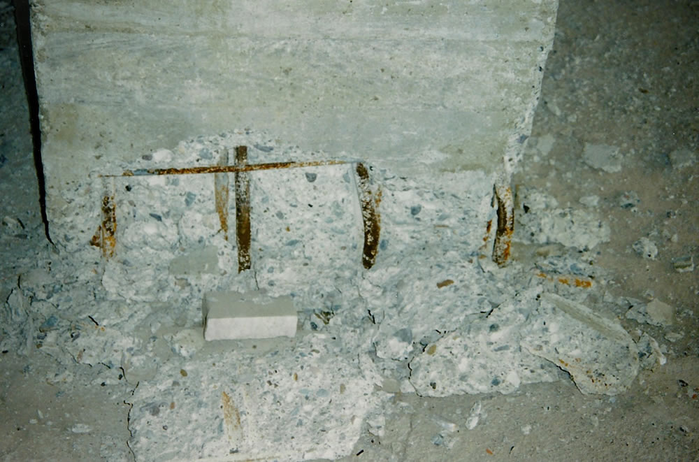 Rebar buckling and spalling concrete at base of column H3 (Photo by Craig Comartin).
