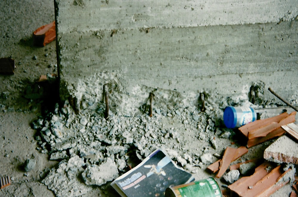 Rebar buckling and spalling concrete at base of column I3 (Photo by Craig Comartin).
