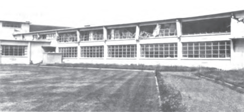 Damage to elevation C of the classroom wing. Minor damage to elevation E of the cafeteria can be seen at left. Above the cafeteria roof, the battering effect of the classroom-wing roof against the gymnasium is visible. (National Academy of Sciences, 1973