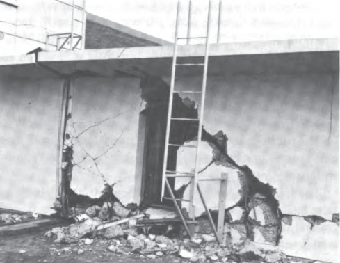 Southwest elevation of classroom wing on second floor and south elevation of upper part of gymnasium (taken from roof of cafeteria). Note the shattering of the concrete in the wall to the right of the expansion joint, and the damage to the reinforced-conc